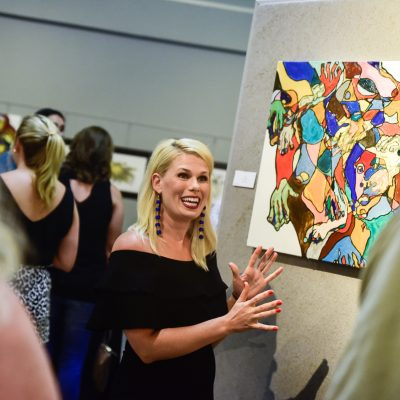 Emmie Sherertz and talks to locals about her work during her opening exhibition at the Columbus Arts Council Friday. The show will be hung in the gallery for the month of July. (Luisa Porter/ Dispatch Staff)