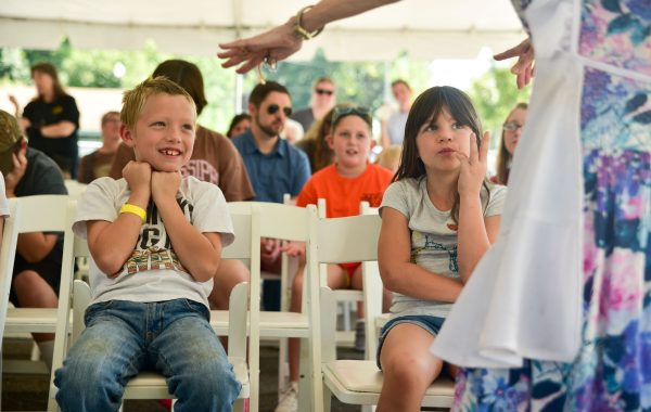 John Gavin Feilds, 7, left, and Cami Knight, 7, pay close attention to the local entertaining story teller, Mother Goose, present a story to an audience at the Farmers Market during the Storytelling Festival Saturday.  John is the grandson of Darlene Wray of Columbus, and Cami is the daughter of Angie and Kenny Knight of Columbus.   (Luisa Porter/ Dispatch Staff)